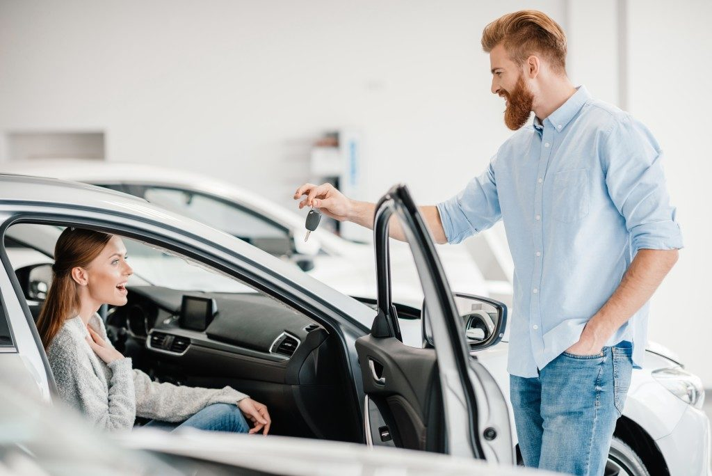 suprised woman and husband handing keys to new car