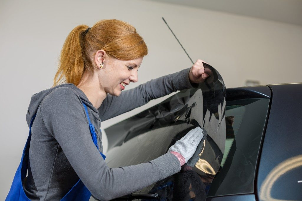 Car wrapper tinting a vehicle window