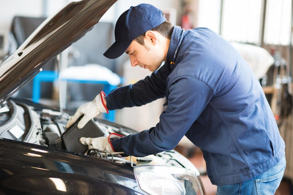 Man in blue uniform doing automotive Servicing