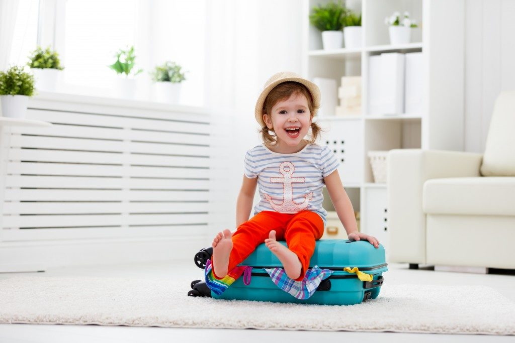 Kid sitting on a luggage filled with clothes