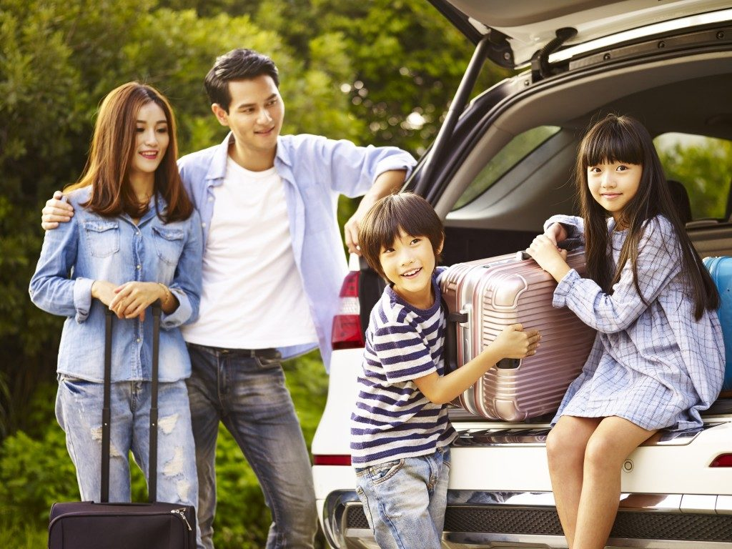 family loading the SUV for a vacation trip