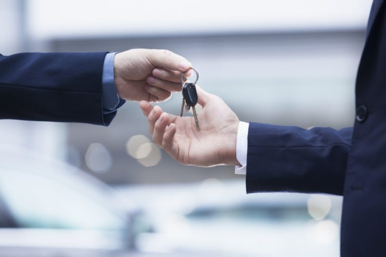salesman handing over keys to new car
