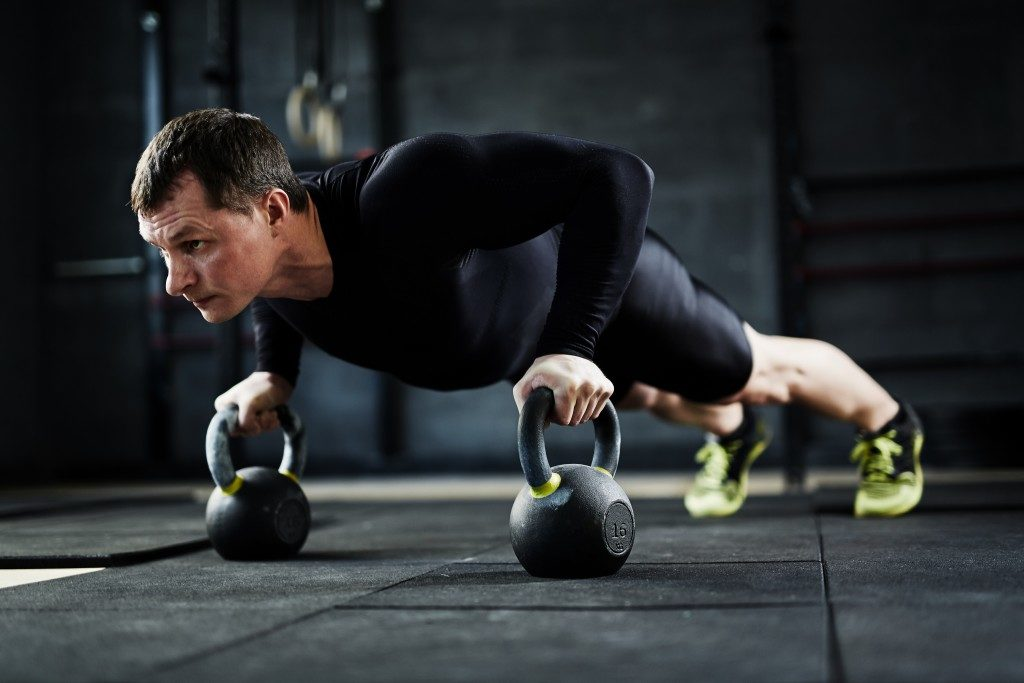 man doing kettlebell pushups
